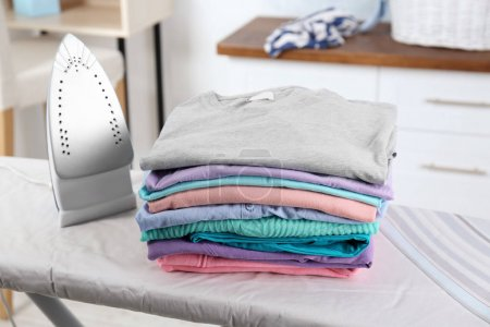 Stack of laundry on ironing board, indoors