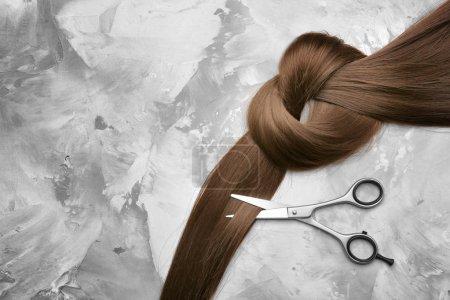 Photo pour Ciseaux professionnels de coiffeur et mèche de cheveux bruns sur fond gris - image libre de droit
