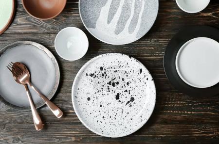 Vaisselle en céramique et couverts sur fond en bois, vue de dessus