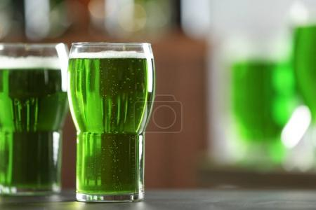 Glass of green beer on table in bar. Saint Patrick's day celebration