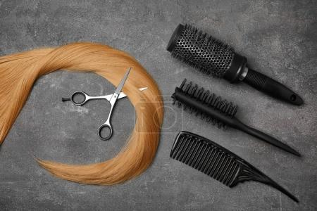 Professional hairdresser's set and strand of blonde hair on grey background