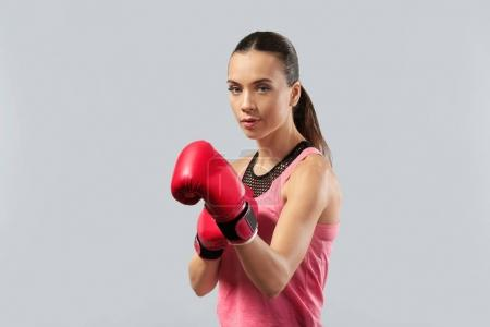 Strong woman in boxing gloves on grey background