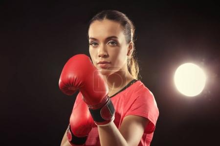 Strong woman in boxing gloves on black background