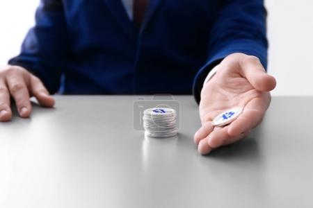 Man with silver bitcoins sitting at table