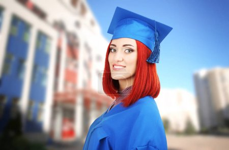 Student in graduation gown and cap on campus territory