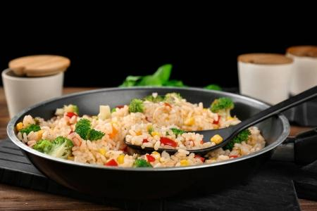 Delicious rice pilaf with broccoli in frying pan on wooden table