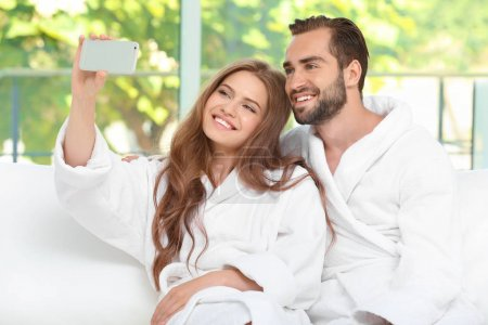 Young loving couple in bathrobes taking selfie at home