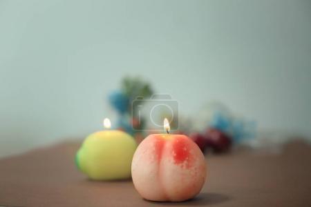 Burning candle in shape of fruit on blurred backgr...