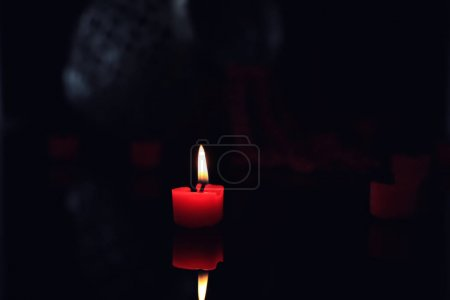 Burning color candle on dark blurred background