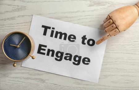 Clock and mannequin hand pointing at sheet of paper with phrase TIME TO ENGAGE on wooden background