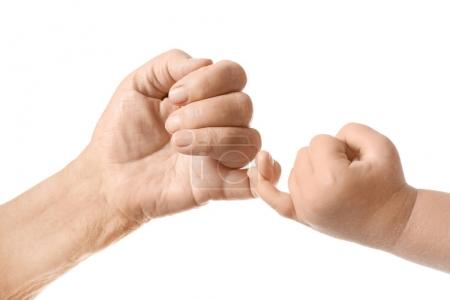 Hands of baby and elderly man making pinkie promise on white background