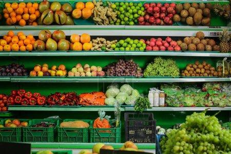 Foto de Variedad de diferentes frutas y vegetales en los estantes de supermercado - Imagen libre de derechos