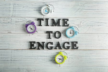 Clocks and phrase TIME TO ENGAGE on wooden background