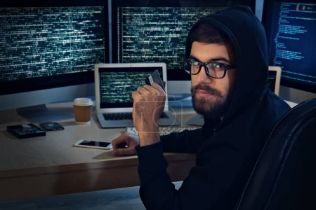 Man with credit card hacking server in dark room