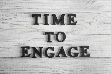 Phrase TIME TO ENGAGE on wooden background