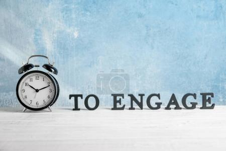 Clock and words composing phrase TIME TO ENGAGE on table