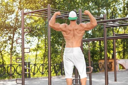 Handsome muscular young man near pull-up bar outdoors