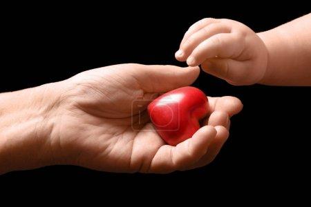 Photo pour Bébé en tenant le petit coeur de main d'un homme âgé sur fond foncé - image libre de droit