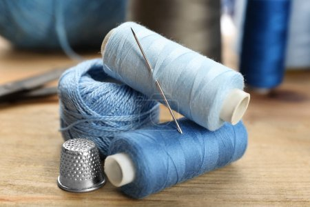 Threads and sewing needle on wooden table, closeup