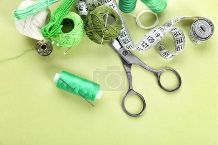 Sewing accessories and threads on color background