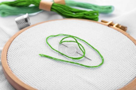 Embroidery hoop with fabric, sewing needle and thread, closeup