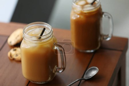 Iced coffee in glass jar with straw on brown wooden table