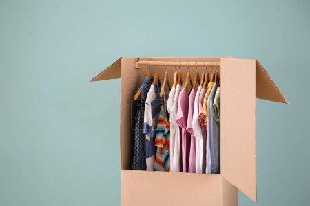 Wardrobe box with clothes on color background