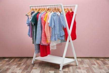 Photo for Rack with different clothes near color wall - Royalty Free Image