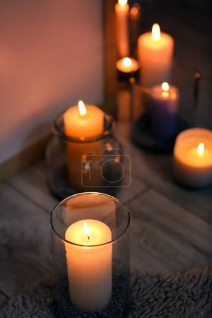 Burning candle on floor indoors