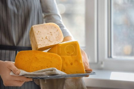 Woman holding tray with variety of cheese near window