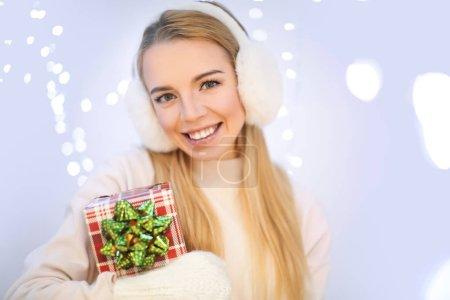Photo pour Femme heureuse avec boîte-cadeau contre Lumières brouillées - image libre de droit