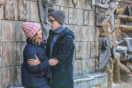 Happy loving young couple near stone wall outdoors