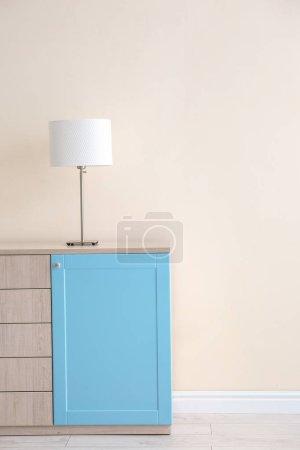 Photo pour Lampe sur armoire en bois près du mur léger - image libre de droit