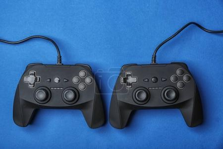 Video game controllers on color background