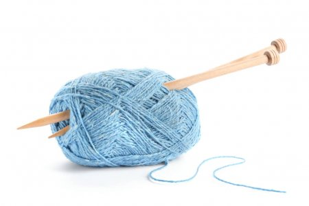 Thread and knitting needles on white background