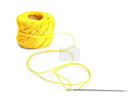 Spool of sewing thread with needle on white background