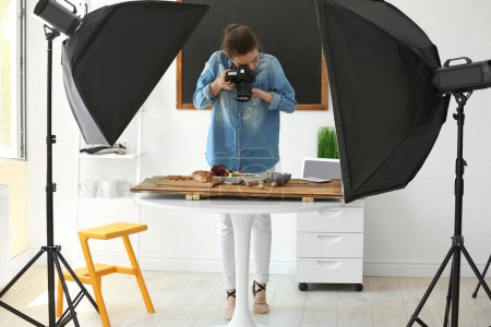 Photo for Young woman with professional camera taking still life pictures in photo studio - Royalty Free Image