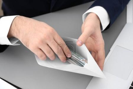Businessman with bribe at table, closeup