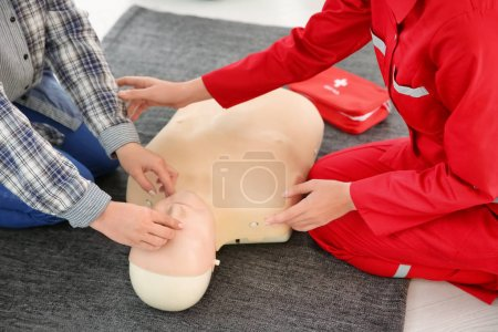 Woman practicing CPR on mannequin in first aid class
