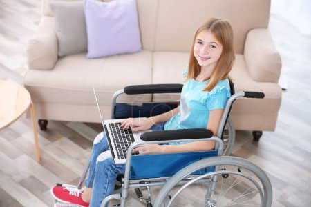 Teenage girl in wheelchair using laptop indoors