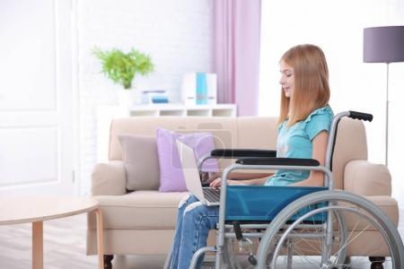Teenage girl in wheelchair using laptop indoors