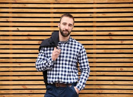 Portrait of young hipster man near wooden wall outdoors