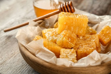 Photo for Bowl with sweet honeycombs on wooden table, closeup - Royalty Free Image