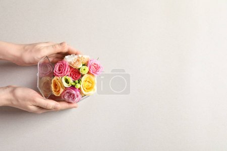 Woman holding box with beautiful roses on light ba...