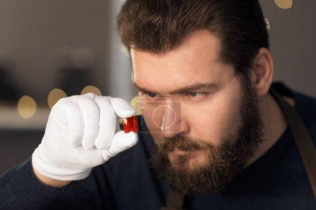 Jeweler holding gem in workshop, closeup