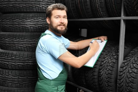 Male mechanic with clipboard near car tires in automobile store