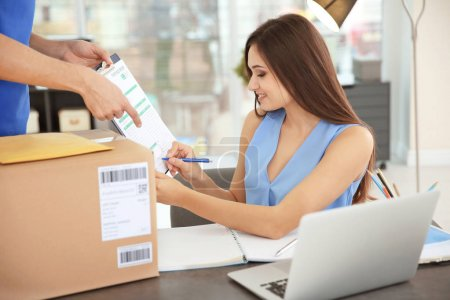 Photo for Woman signing documents after receiving parcel from courier - Royalty Free Image