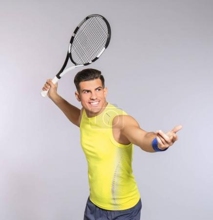 Portrait of handsome man playing tennis against grey background