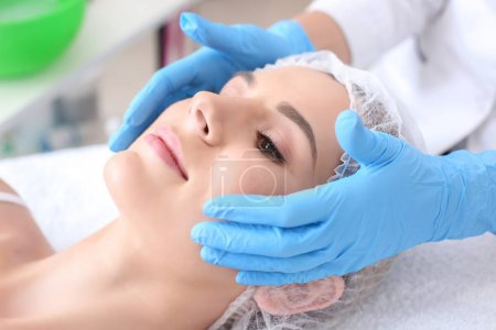 Young woman undergoing beauty procedure in salon