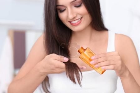 Young woman applying oil onto her hair, indoors